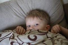 Dziecko budzi się up out spod koc i zerknięcia zdjęcia stock