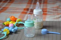 Dziecko butelka z mlekiem i łyżką w dla tła dziecko mrówka bawi się Obraz Stock