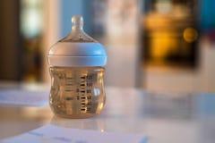 Dziecko butelka z sutkiem i wodą na bielu stole zdjęcie stock