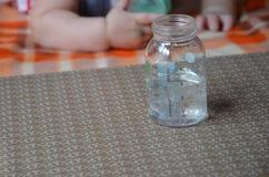 Dziecko butelka z wather i łyżką w dla tła dziecko mrówka bawi się Zdjęcie Stock