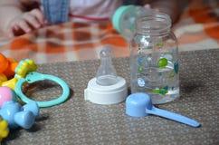 Dziecko butelka z wather i łyżką w dla tła dziecko mrówka bawi się Fotografia Stock