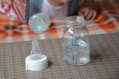 Dziecko butelka z wather i łyżką w dla tła dziecko mrówka bawi się Zdjęcia Royalty Free
