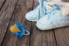 Dziecko buty i pacyfikator na starym drewnianym tle zdjęcia royalty free