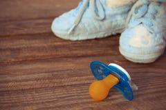 Dziecko buty i pacyfikator na starym drewnianym tle obraz royalty free