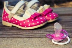 Dziecko buty i pacyfikator na starym drewnianym tle fotografia royalty free