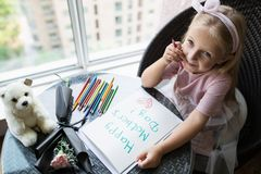 Dziecko córki obrazu pocztówka dla mamy Dziewczyna siedzi w domu na stole, następne lying on the beach menchie kwitnie dla matki  fotografia royalty free