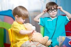 Dziecko chłopiec bawić się doktorski indoors i leczyć mokiet zabawkę zdjęcie royalty free