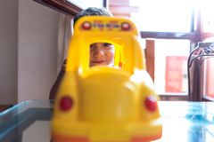 Dziecko chłopiec bawić się z autobus szkolny zabawką indoors zdjęcie royalty free