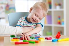 Dziecko chłopiec bawić się z glinianym ciasta, edukaci i daycare pojęciem, zdjęcia royalty free