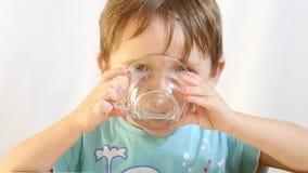 Dziecko chłopiec cieszy się pijący herbaty od szklanego filiżanki zakończenia zdjęcie wideo