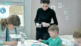 Dziecko chłopiec siedzi wpólnie wokoło stołu w sala lekcyjnej i rysunku Z one są ich piękny nauczyciel i potomstwa zbiory wideo