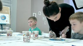 Dziecko chłopiec siedzi wpólnie wokoło stołu w sala lekcyjnej i rysunku Z one są ich piękny nauczyciel i potomstwa zbiory
