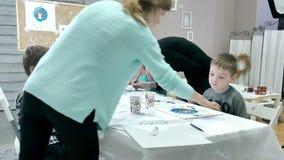 Dziecko chłopiec siedzi wpólnie wokoło stołu w sala lekcyjnej i rysunku Z one są ich piękny nauczyciel i potomstwa zdjęcie wideo