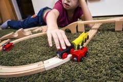 Dziecko chłopiec sztuka z drewnianym pociągiem, budowy zabawkarska linia kolejowa w domu lub zdjęcie stock