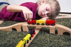 Dziecko chłopiec sztuka z drewnianym pociągiem, budowy zabawkarska linia kolejowa w domu lub zdjęcie royalty free