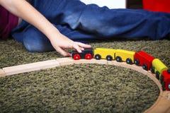 Dziecko chłopiec sztuka z drewnianym pociągiem, budowy zabawkarska linia kolejowa w domu lub obraz royalty free