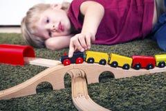 Dziecko chłopiec sztuka z drewnianym pociągiem, budowy zabawkarska linia kolejowa w domu lub fotografia stock