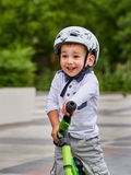 Dziecko chłopiec w białej hełm jazdie na jego pierwszy rowerze z hełmem rower bez następów Fotografia Stock