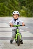Dziecko chłopiec w białej hełm jazdie na jego pierwszy rowerze z hełmem rower bez następów Zdjęcia Stock