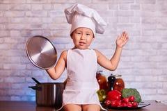 Dziecko, chłopiec w fartuchu, siedzi na kuchennym stole w kucharza nakrętce, chwyty dekiel, obok on jest drewnianymi łyżkami i ro obrazy stock