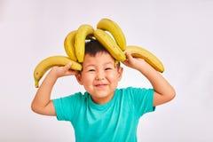Dziecko chłopiec w turkusowej koszula, głowie na bananach i zdrowym jedzeniu, - owocowych obrazy royalty free