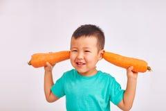 Dziecko chłopiec w turkusowej koszula, pokrywa ucho z ogromnymi marchewkami i zdrowym jedzeniu, - owoc fotografia stock