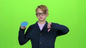 Dziecko chłopiec z szkła patrzejącą kredytową kartą i pokazywać niechęć na zieleniejemy ekran swobodny ruch zbiory