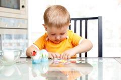 Dziecko chłopiec dekoruje Easter jajka indoors Fotografia Royalty Free