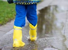 Dziecko chodzi w kałuży w podeszczowych butach Zdjęcie Royalty Free