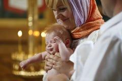 Dziecko chrzcił mamą w ona ręki Zdjęcia Stock