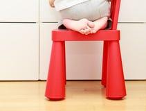Dziecko cieki na dziecka krześle, dzieciaki stwarzają ognisko domowe zbawczego pojęcie Zdjęcie Royalty Free
