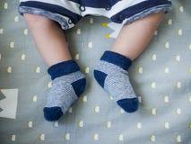 Dziecko cieki w błękitnych skarpetach utrzymuje dziecko cieki ciepli Fotografia Royalty Free