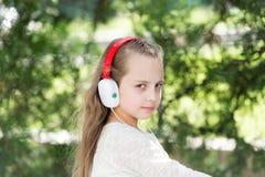 Dziecko cieszy się muzykę w hełmofonach plenerowych Mała dziewczynka słucha muzykę w lato parku Moda dzieciak i nowożytna technol fotografia royalty free