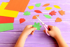 Dziecko ciie out barwiącego papierowego liść Dziecko trzyma nożyce i zielonego liść w jego ręki Barwiony papieru set, kolorowi li Zdjęcie Stock
