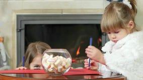 Dziecko coś poczynał od behind, dziewczyna z twarzy szczwanymi spojrzeniami out jego biurko, mała dziewczynka remis pióro na prze zbiory wideo