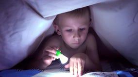Dziecko czyta książkę pod koc z latarką przy nocą chłopiec z lekkim włosy i niebieskimi oczami zbiory wideo