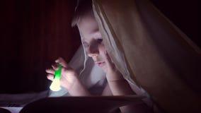Dziecko czyta książkę pod koc z latarką przy nocą chłopiec z lekkim włosy i niebieskimi oczami zdjęcie wideo