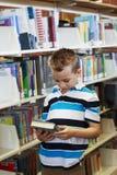 Dziecko czyta książkę przy biblioteką Zdjęcie Royalty Free