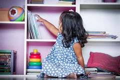 Dziecko czyta, śliczna mała dziewczynka wybiera książkę na półka na książki Fotografia Royalty Free