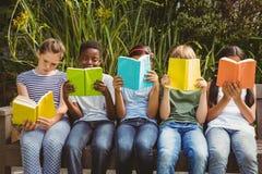 Dziecko czytelnicze książki przy parkiem Zdjęcie Royalty Free
