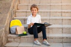 Dziecko czytelnicze książki Ucznie robi pracie domowej outdoors fotografia stock