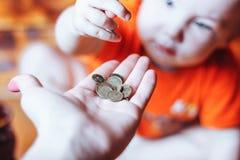 Dziecko daje monetom jego matka Obrazy Stock