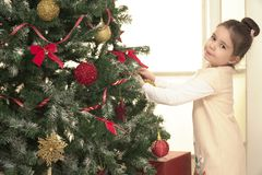 Dziecko dekoruje Xmas drzewa w rodzinnym żywym pokoju zdjęcie stock