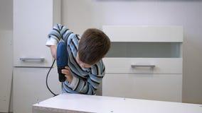 Dziecko domowe rutyny, sprawny dziecko z elektrycznym świderem podczas zgromadzenie drewniany meble w pokoju zdjęcie wideo