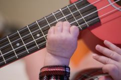 Dziecko dotyka sztuki gitarę Ukulele zawiązuje i gryźć obrazy royalty free