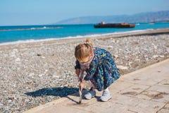 Dziecko, dzieciństwo i ludzie pojęć, - dziewczynka siedzi na asfaltu kwadrata sztuce z kijem i drodze blisko morze plaży Obraz Royalty Free