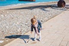 Dziecko, dzieciństwo i ludzie pojęć, - dziewczynka siedzi na asfaltu kwadrata sztuce z kijem i drodze blisko morze plaży Zdjęcie Stock