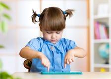 Dziecko dziewczyna bawić się z cyfrowym pastylka komputerem osobistym przy Zdjęcie Royalty Free