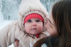Dziecko dziewczyna bawić się z jej mamą w zima lesie fotografia stock