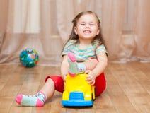 Dziecko dziewczyna bawić się z zabawkarskim samochodem na podłoga obraz stock